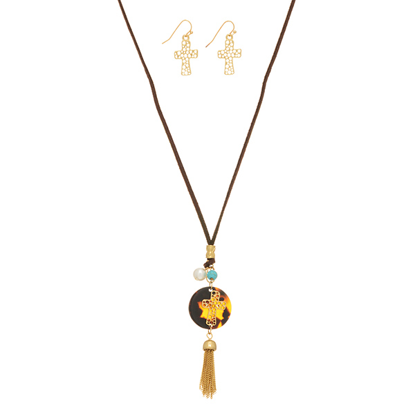 "Brown cord necklace set featuring a tortoise disk with a gold tone cross and dangling tassel. Approximately 20"" in length."