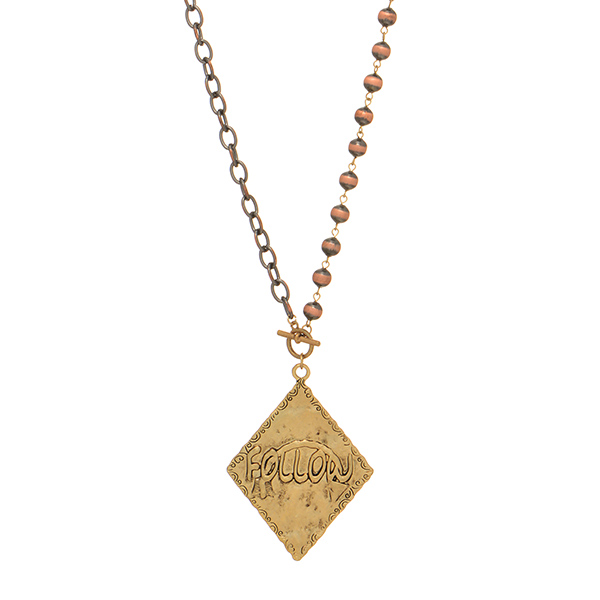 """Copper tone toggle necklace featuring a gold tone pendant with an arrow stamped """"FOLLOW"""". Approximately 29 1/2"""" in length."""
