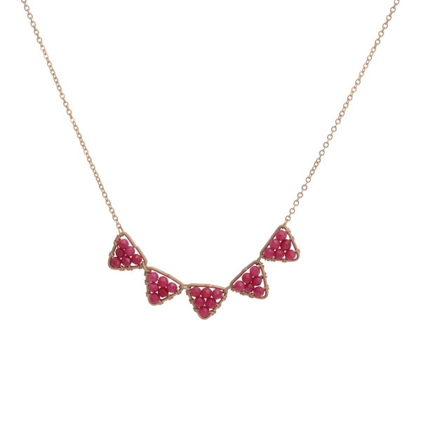 "Burnished gold tone necklace featuring wire wrapped fuchsia beads a triangular castings. Approximately 16"" in length."