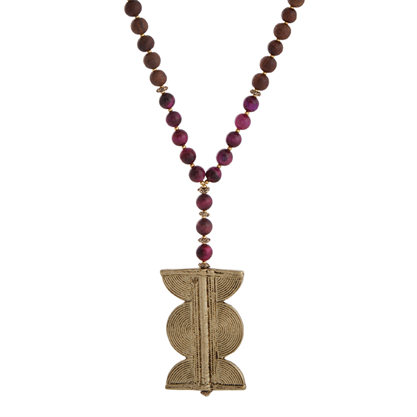 """Burnished gold tone half beaded necklace displaying fuchsia and brown wood beads with a 2 1/2"""" gold tone pendant. Approximately 35"""" in length. Handmade in the USA."""