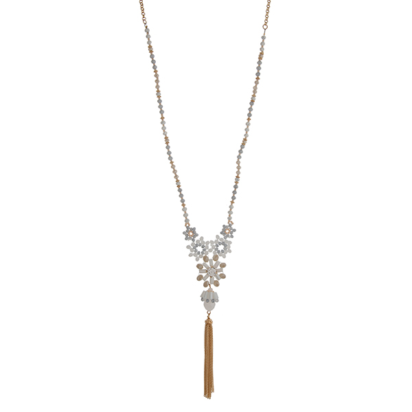 "Gold tone half beaded necklace with white and gray beads displaying flowers with a rhinestone and hanging chain tassel. Approximately 30"" in length."