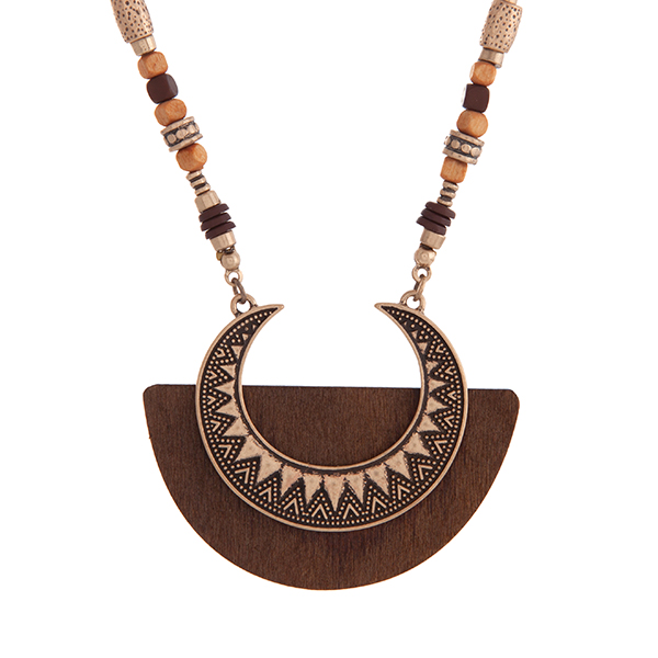 """Burnished gold tone bohemian style necklace with brown and wood beads and a crescent shaped pendant on brown wood. Approximately 29"""" in length."""