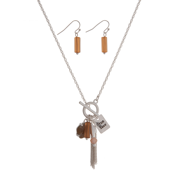 "Matte silver tone toggle necklace set with a brown stone, a topaz bead, a chain tassel, and a plate stamped ""True love"". Approximately 16"" in length."