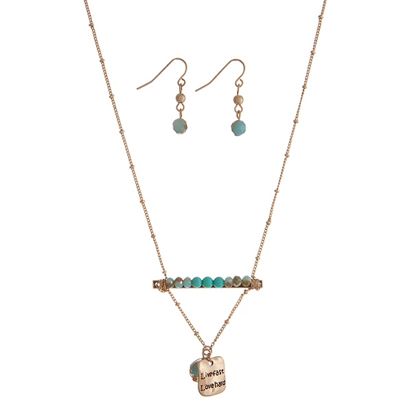 "Gold tone necklace set displaying a bar with turquoise beads and a hammered plate stamped ""Live fast Love hard"". Approximately 17"" in length."