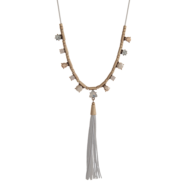 """White cord necklace displaying white, tan, and clear cabochons with a white leather tassel and gold tone accents. Approximately 30"""" in length."""
