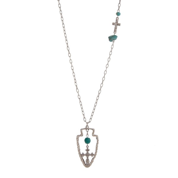 """Burnished silver tone necklace displaying a hammered cross station with a turquoise stone and bead and a wire wrapped arrowhead pendant with a turquoise bead and hanging cross. Approximately 29"""" in length."""