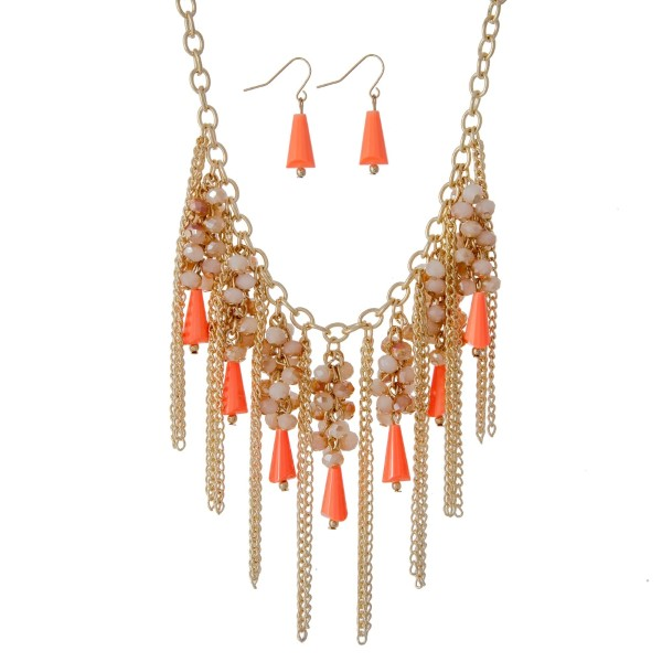 "Gold tone statement necklace set with ivory and bright coral beads and metal chain fringe. Approximately 18"" in length."