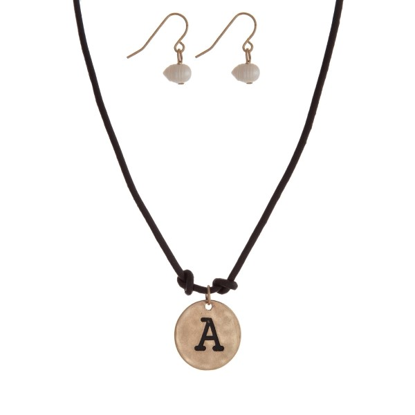 "Brown cord necklace with a gold tone pendant stamped with the letter ""A"" and a pearl closure. Approximately 18"" in length."
