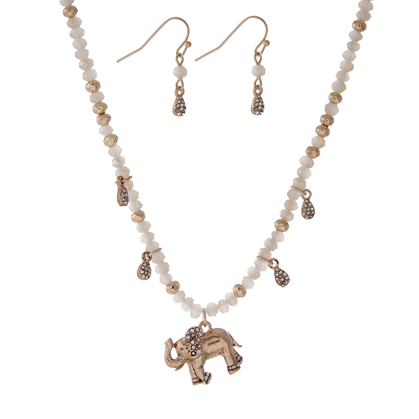 """Gold tone necklace with white faceted beads and an elephant pendant. Approximately 18"""" in length."""