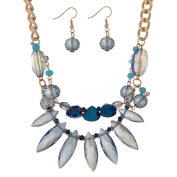 """Gold tone necklace set displaying blue glass beads and matching fishhook earrings. Approximately 18"""" in length."""