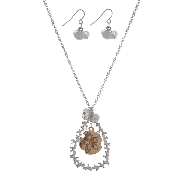 "Silver tone necklace set with a two tone sand dollar and coral reef teardrop pendant, accented with a white opal bead. Approximately 18"" in length."