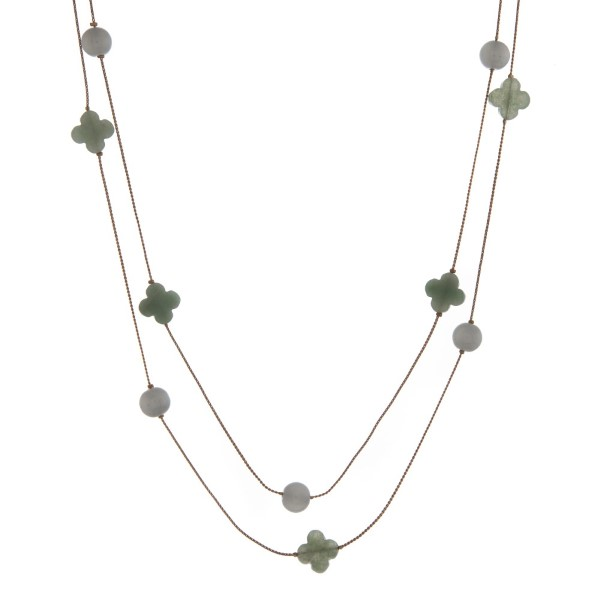"Dainty gold tone wrap necklace with jade beads and quatrefoil stones. Approximately 60"" in length."