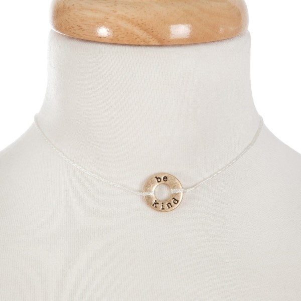 """White cord necklace with a gold disc pendant, stamped with """"be kind."""" Approximately 14"""" in length."""
