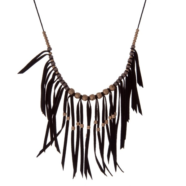 """Adjustable black cord necklace with black fringe and gold tone bead accents. Approximately 36"""" in length."""