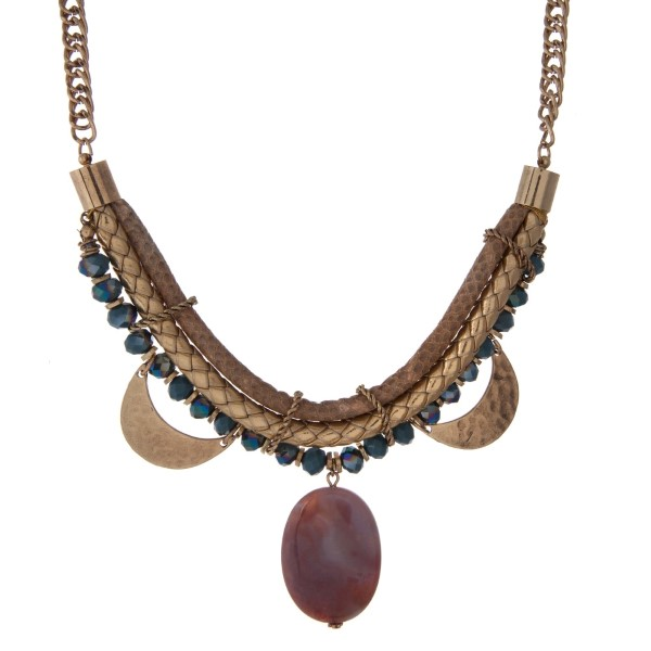 """Gold tone statement necklace with a snake skin pattern, hammered gold tone half circles, blue faceted beads and a purple stone pendant. Approximately 16"""" in length."""