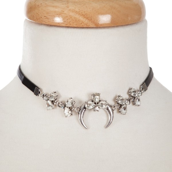 "Black faux leather choker with a silver tone crescent focal, accented with clear rhinestones. Approximately 12"" in length."