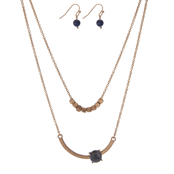 "Dainty gold tone, double layer necklace set with a blue stone and gold square beads. Approximately 16"" in length."