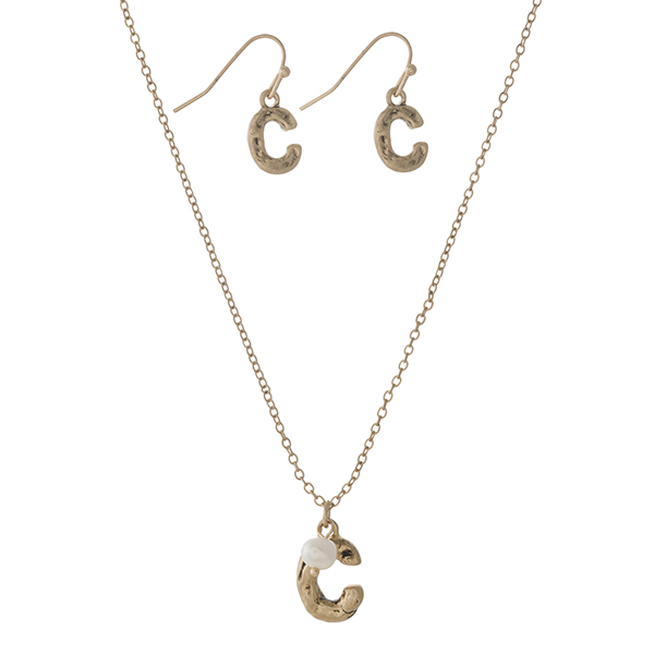 "Burnished gold tone necklace set with a block 'C' initial, accented by a freshwater peal bead and matching fishhook earrings. Approximately 16"" in length."