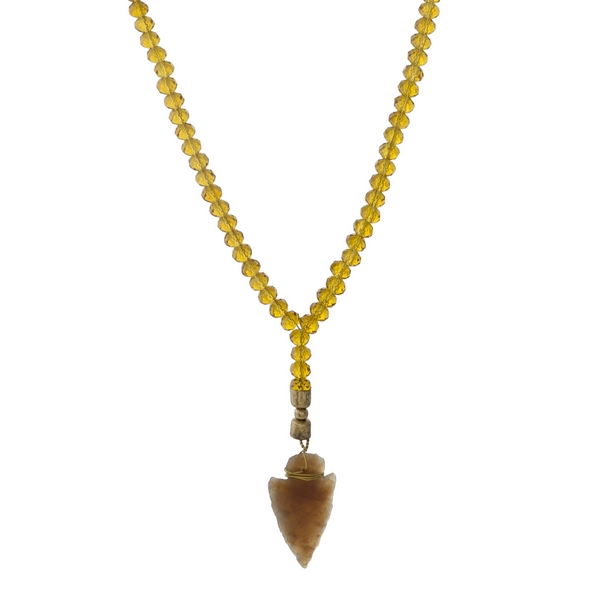 """Brown faux suede and topaz beaded necklace with an arrowhead pendant. Approximately 36"""" in length."""