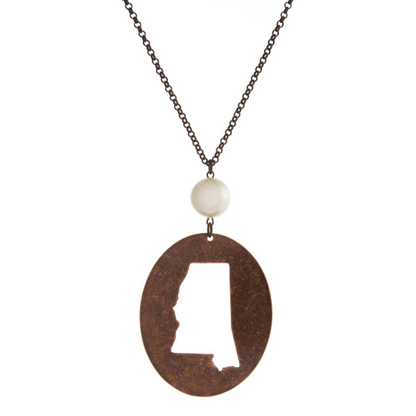 "Burnished copper tone necklace with a Mississippi cutout pendant accented by a pearl bead. Approximately 30"" in length. Oval pendant is approximately 2.5"" tall."