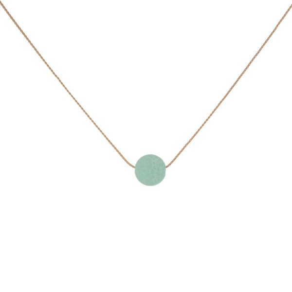 """Dainty gold tone necklace with a natural stone bead pendant. Approximately 16"""" in length. Natural stone colors may vary."""