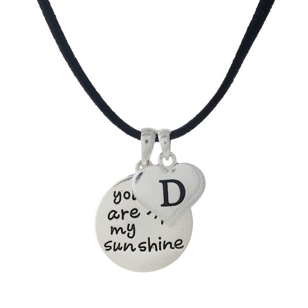 "Black faux suede cord necklace displaying a silver tone circle pendant stamped with ""You are my sunshine"" and a heart pendant stamped with the letter 'D' initial. Approximately 18"" in length."
