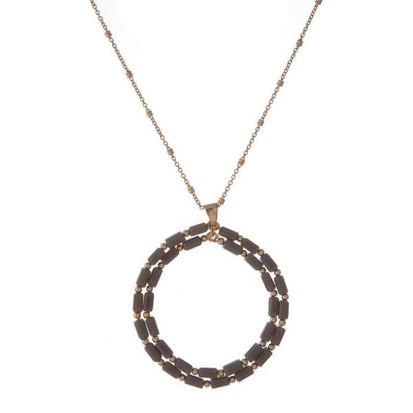 "Gold tone necklace featuring a gray beaded, open circle pendant. Approximately 32"" in length."