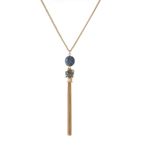 "Gold tone necklace featuring a blue natural stone pendant and chain tassel. Approximately 30"" in length."