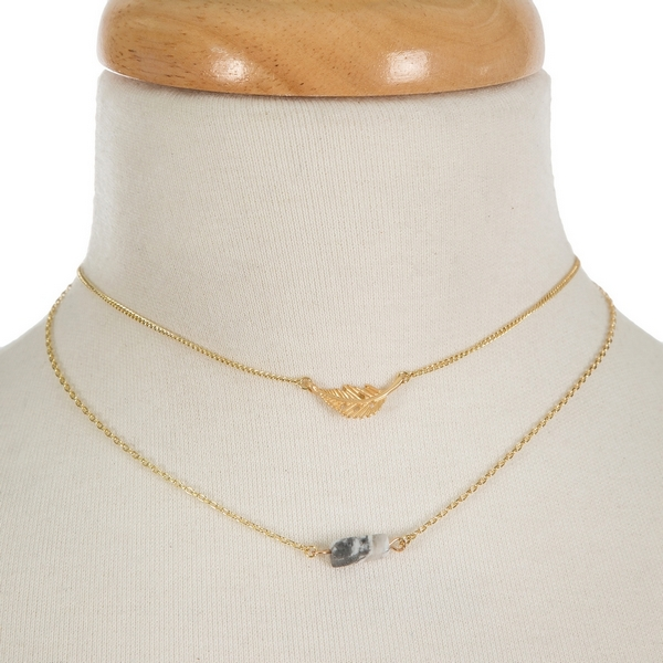 "Dainty gold tone, two layer necklace featuring a feather pendant and a gray stone pendant. Approximately 14"" and 15"" in length."