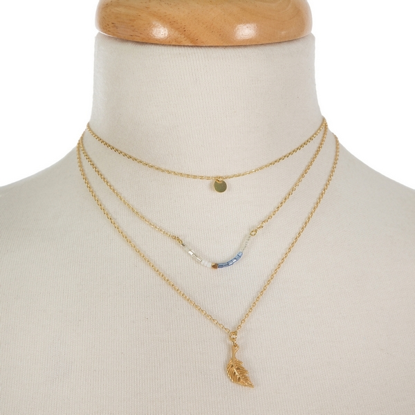 "Dainty gold tone three layer necklace featuring a blue and white beaded curved bar pendant and a feather pendant. Approximately 12"" to 16"" in length."