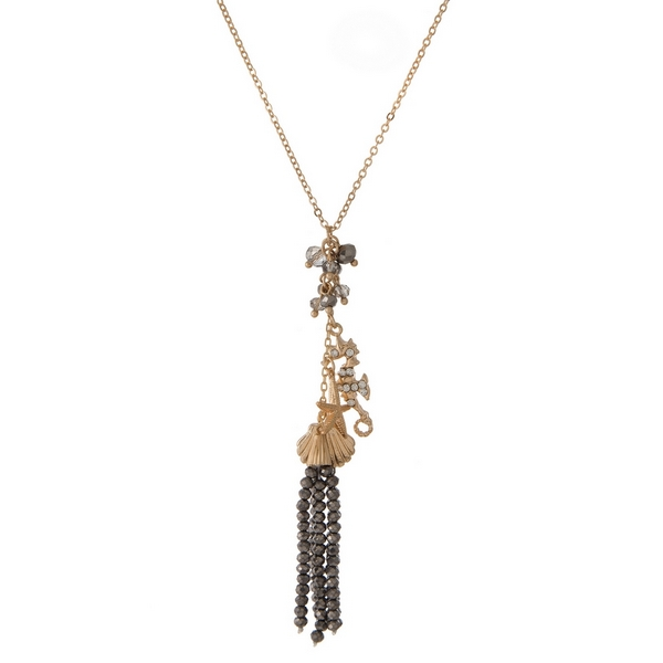 "Gold tone necklace featuring a hematite beaded tassel pendant, accented with seashell, starfish, and seahorse charms. Approximately 20"" in length."