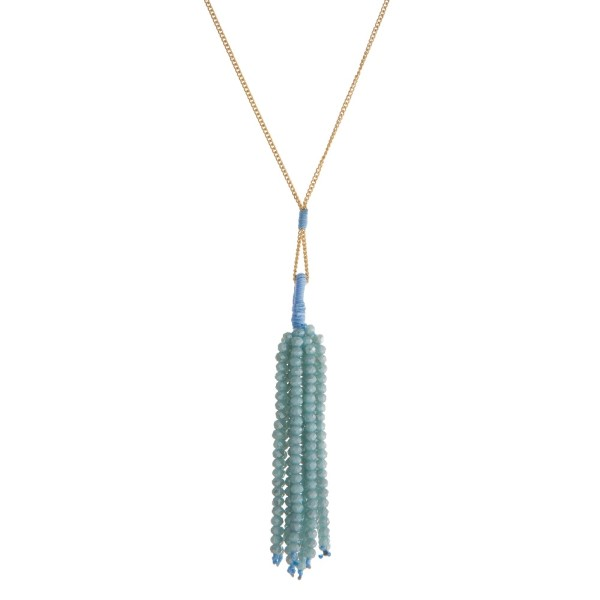 "Dainty gold tone necklace with an aqua faceted bead tassel. Approximately 28"" in length."