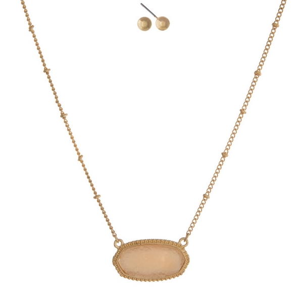"Gold tone necklace set featuring an ivory faux druzy stone and matching stud earrings. Approximately 16"" in length."