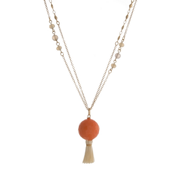 "Gold tone necklace featuring gray faceted beads, a coral bead pendant and an ivory tassel. Approximately 36"" in length."