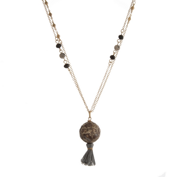 """Gold tone necklace featuring black faceted beads, a gray and brown marbled bead pendant and a gray tassel. Approximately 36"""" in length."""