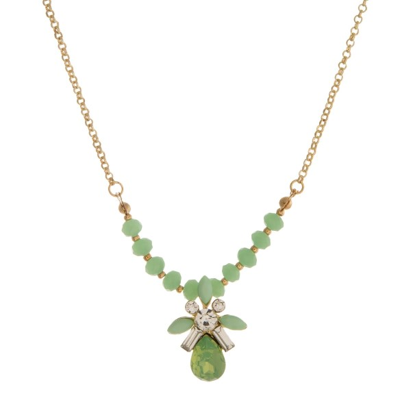 "Gold tone necklace with light green beads and a light green rhinestone pendant. Approximately 16"" in length."