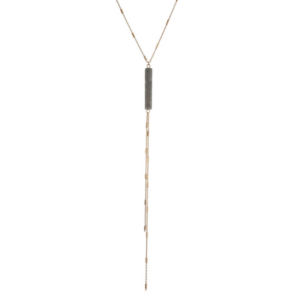 "Dainty gold tone necklace with a gray natural stone pendant and a chain tassel. Approximately 22"" in length."