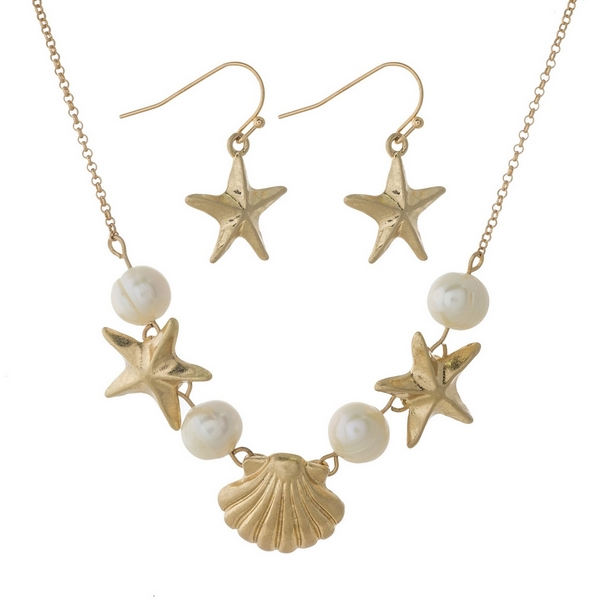 "Gold tone necklace set with freshwater pearl beads, starfish, seashells and matching fishhook earrings. Approximately 16"" in length."