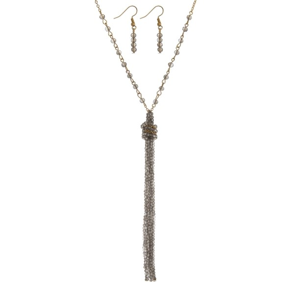 """Gold tone necklace set with a beaded gray tassel and matching fishhook earrings. Approximately 30"""" in length."""