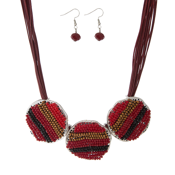 "Burgundy waxed cord necklace set with three red and burgundy beaded circles, and matching fishhook earrings. Approximately 16"" in length."