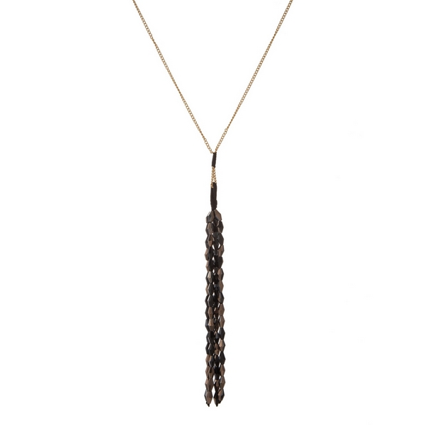 """Gold tone necklace with a black faceted bead tassel pendant. Approximately 30"""" in length."""