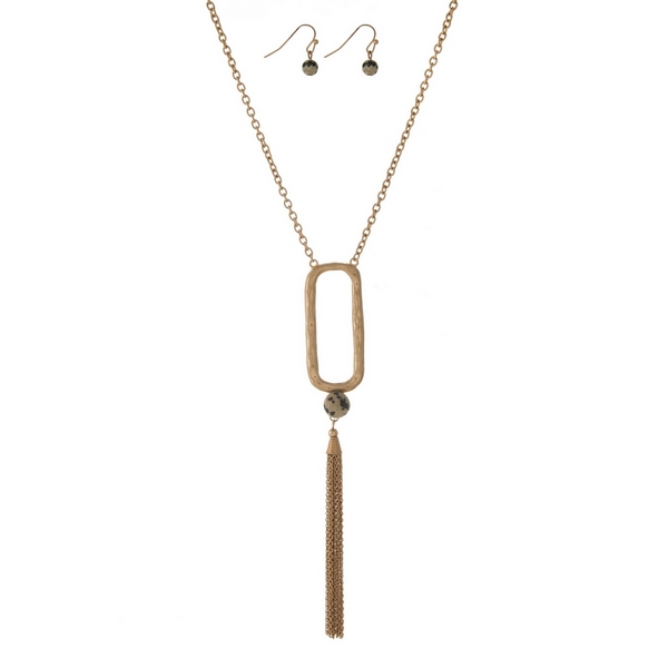 """Gold tone necklace with an open oval shape, a chain tassel and a dalmatian jasper natural stone bead. Approximately 32"""" in length."""