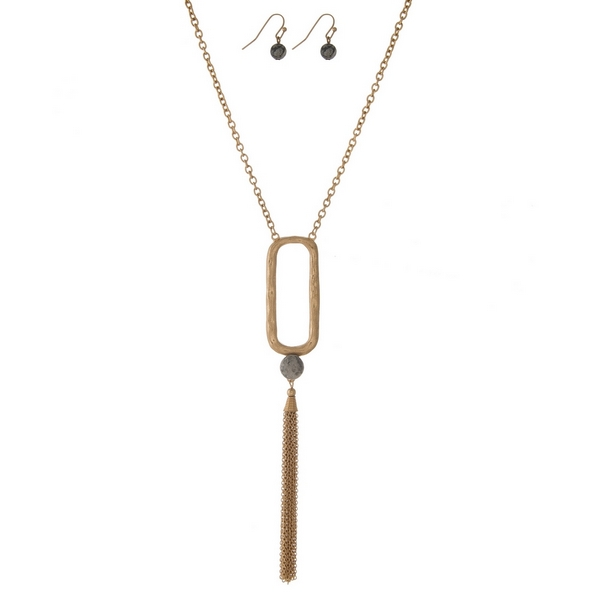 """Gold tone necklace with an open oval shape, a chain tassel and a gray jasper natural stone bead. Approximately 32"""" in length."""