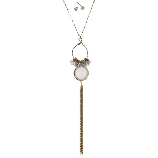 """Burnished gold tone necklace set with gray beads, a faux druzy stone and a chain tassel. Approximately 30"""" in length."""