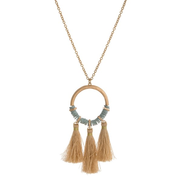 """Gold tone necklace with a beaded circle pendant and thread tassels. Approximately 30"""" in length."""