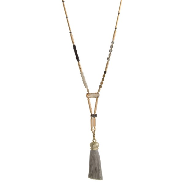 """Gold tone necklace with natural stone beads and a thread tassel. Approximately 28"""" in length. Handmade in the USA."""