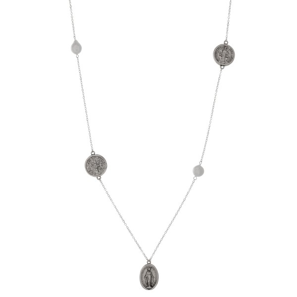 "Dainty metal necklace with freshwater pearl beads, coin stationaries and a Miraculous Medal pendant. Approximately 28"" in length."