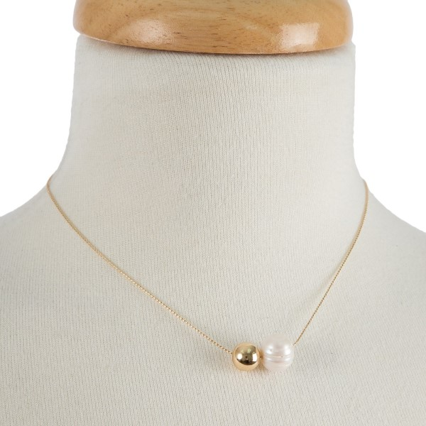 "Dainty, metal necklace with a pearl and circle detail. Approximately 14"" in length."