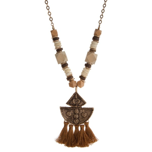 """Long necklace with wooden beads and boho pendant accents with soft tassels. Approximately 32"""" in length."""