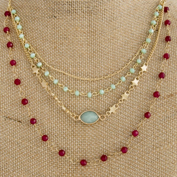 "Gold tone layered necklace with natural stone beads and star details. Approximately 18"" in length."